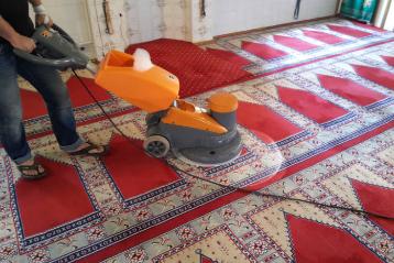 Cami halısını yerinde makine ile temizleyen bir görevli