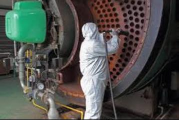 Fabrikada büyük bir makine ve onu temizleyen beyaz tulum giymiş bir adam