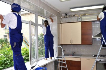 Bir evin mutfağını temizleyen tulum giymiş temizlik elemanları